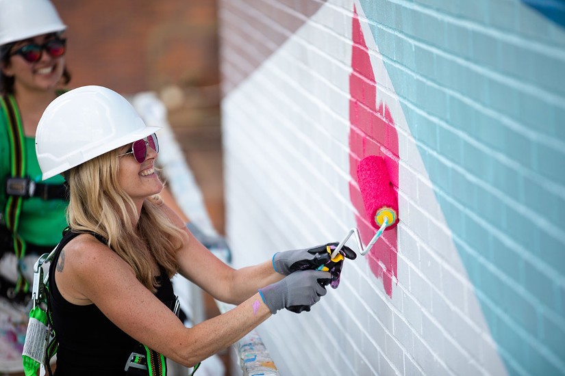 Artist Rebecca Rustein works on her mural Convergence, July 12, 2019. Photo by Steve Weinik.